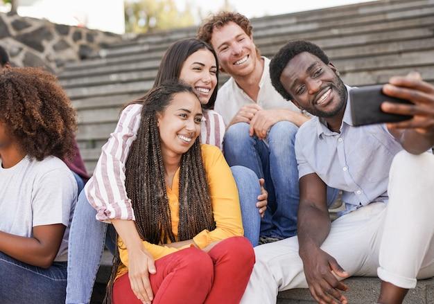 屋外でスマートフォンを使って自分撮りをしている若い多民族の友人-街で一緒にミレニアル世代の人々