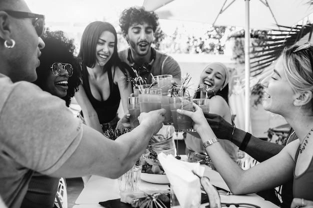 Молодые многорасовые друзья поджаривают пиво на вечеринке с барбекю в саду
