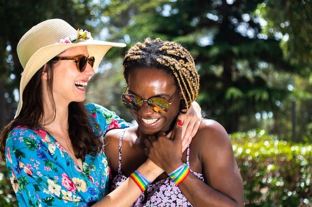 Молодая многорасовая лесбийская пара смеется вместе во время отпуска летняя лгбт-концепция любовь
