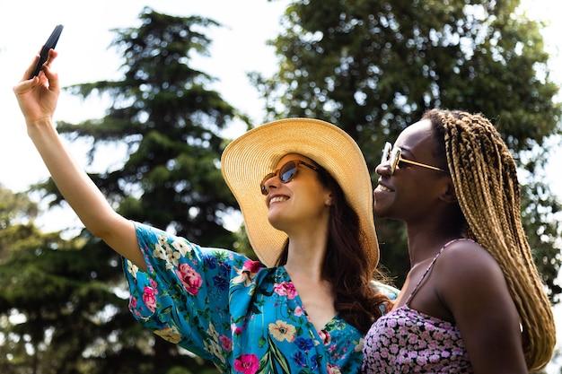 Молодая многорасовая лесбийская пара делает селфи с мобильным телефоном во время каникул лгбт-летнее время
