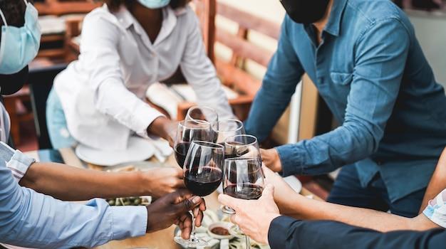 Молодые многорасовые люди аплодируют вином в защитных масках - концепция социальной дистанции - сосредоточение внимания на нижней белой руке