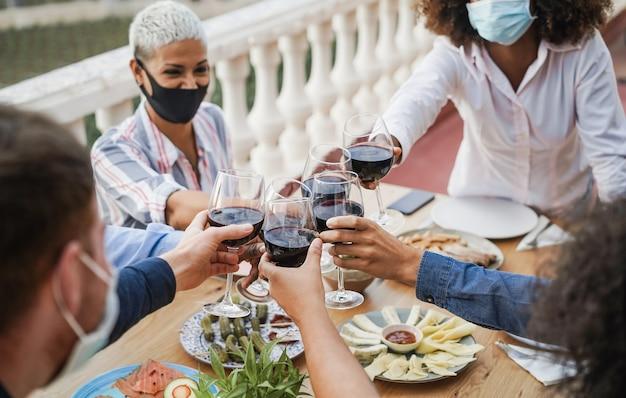 보호 마스크를 착용하는 동안 와인을 응원하는 젊은 다민족 사람들