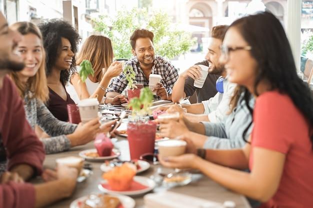 브런치를 먹고 바 레스토랑에서 스무디를 마시는 젊은 다민족 사람들-아시아 사람 얼굴에 초점