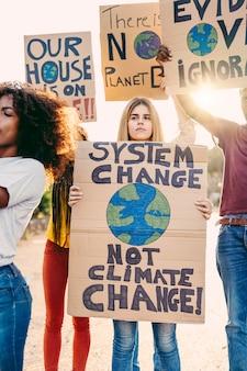 다른 문화와 인종의 젊은 다인종 사람들이 도시에 배너를 들고 기후 변화를 보여줍니다