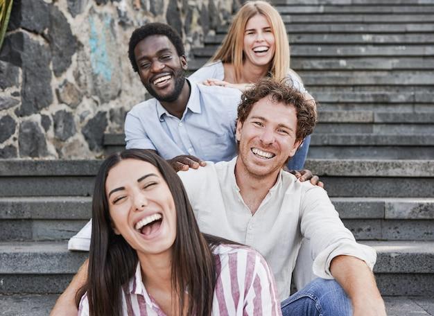 街の階段に座ってカメラに微笑んでいる若い多民族の人々-ミレニアル世代の友人と多様性の概念