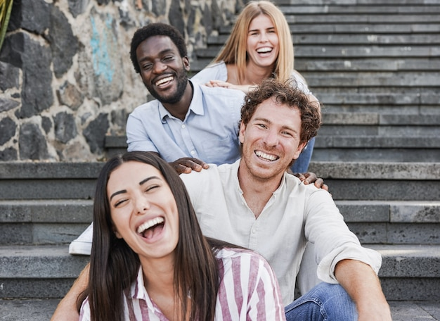 Young multiracial people sitting on stairs in the city and smiling on camera - millennial friends and diversity concept