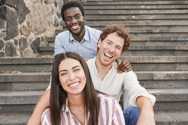 Young multiracial people sitting on stairs in the city while smiling on camera - friendship and diversity
