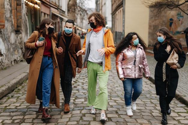 Молодые многорасовые люди в медицинских масках во время прогулки по улице. мужчины и женщины разговаривают и улыбаются в свободное время на открытом воздухе.