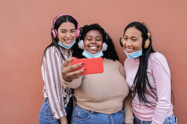 Young multiracial people wearing safety masks while taking selfie with mobile phone outdoor - main focus on center girl
