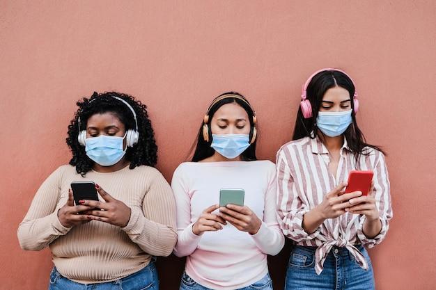 屋外で携帯電話を使用しながら安全マスクを着用している若い多民族の人々-センターガールに主な焦点