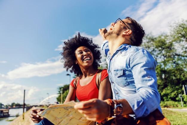 Молодые многорасовые туристы сидят на открытом воздухе, улыбаются и изучают карту.