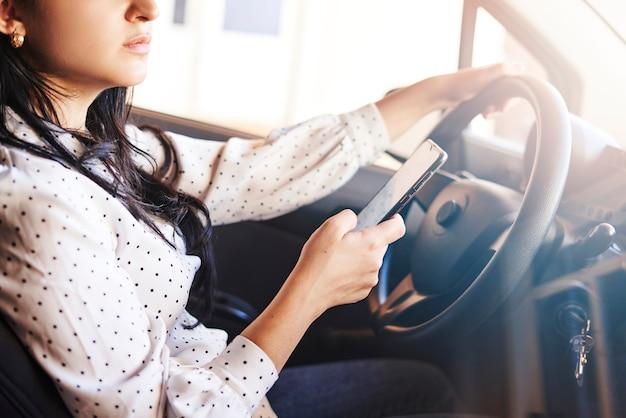 젊은 다민족 여성 문자 메시지 및 자동차 운전 자동차를 운전하는 동안 휴대폰을 사용하는 여성