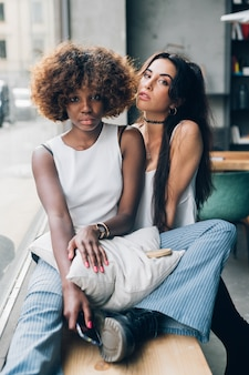 Young multiracial women sitting and looking camera in bright apartment