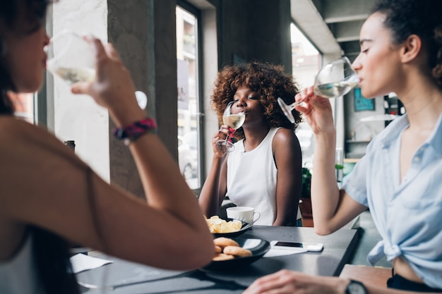 Young multiracial women sitting in modern restaurant drinking together wine
