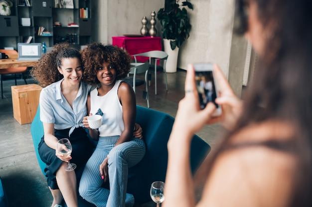 Young multiracial women taking photo and having fun in modern loft