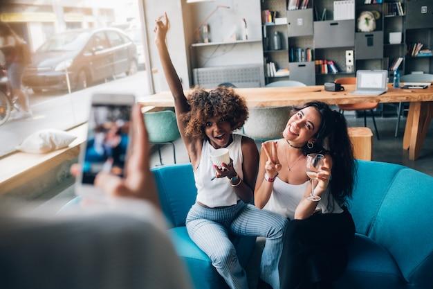 Young multiracial women taking photo and having fun in modern pub