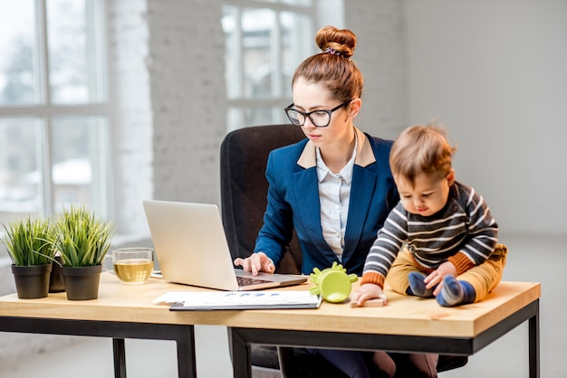Молодой многозадачный бизнесмен, одетый в костюм, работающий с ноутбуком и документами, сидит со своим маленьким сыном в офисе