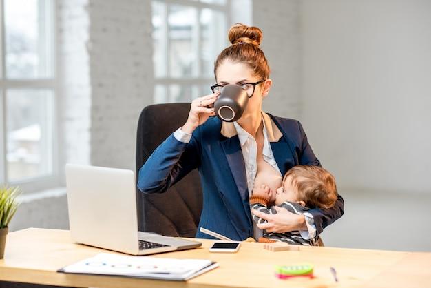 Молодой многозадачный бизнесмен кормит своего маленького сына грудью во время перерыва, попивая кофе в офисе