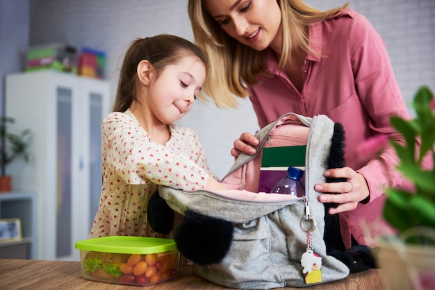 Young mum and daughter packing backpack for the school
