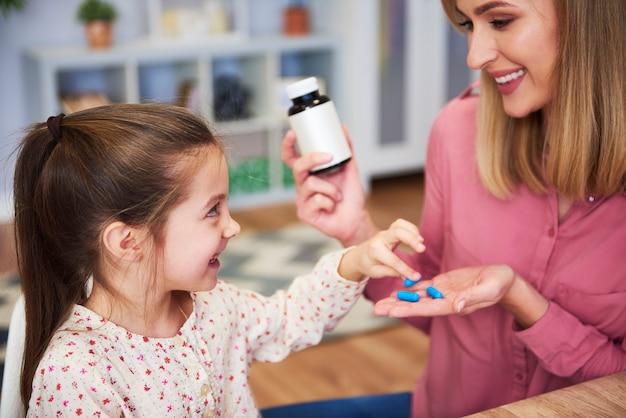 어린 딸에게 약을 주는 젊은 엄마