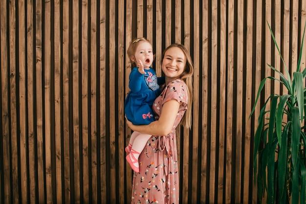 若い母は木製の壁の上の手で彼女の娘を保持します