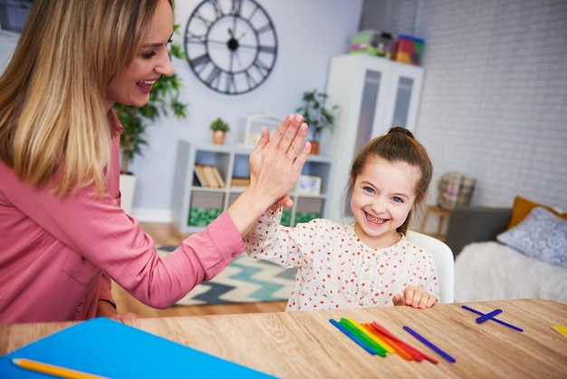 Young mum teaching child at home