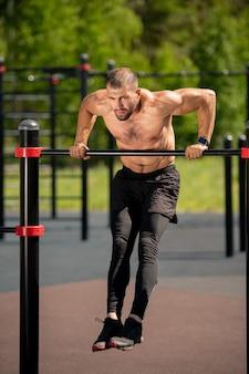 運動中に地面にぶら下がっている間にスポーツバーを曲げる若い筋肉アスリート