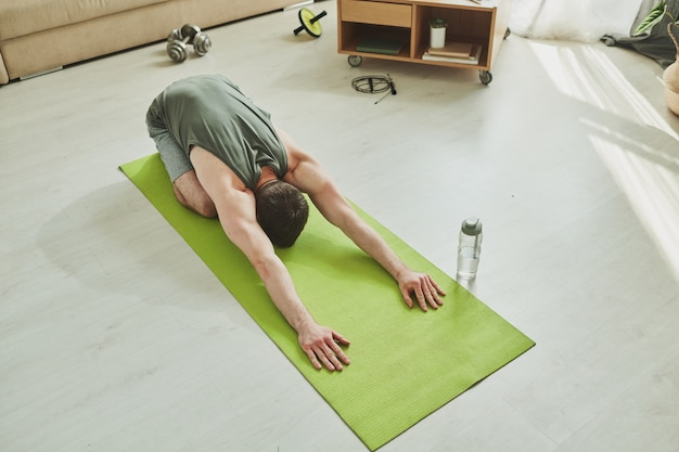 Young muscular athlete doing relaxation exercise on mat while standing on his knees with arms stretched forwards during home workout