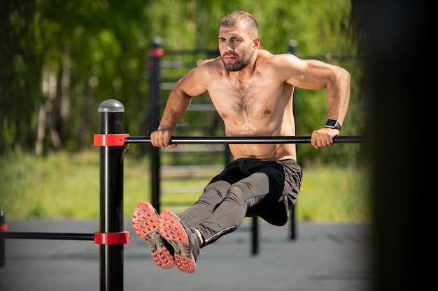 地面に足を前に伸ばしながらスポーツバーで運動している若い筋肉アスリート