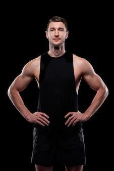 검은 조끼와 반바지에 고립 된 서있는 동안 허리에 손을 유지하는 젊은 근육 운동 선수