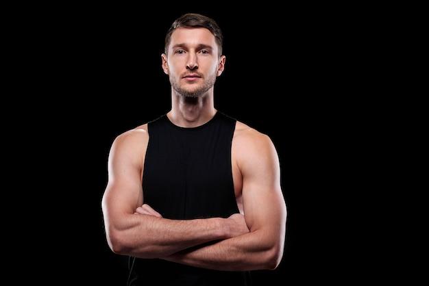격리 된 상태로 서있는 동안 가슴으로 팔을 교차하는 검은 조끼에 젊은 근육 운동 선수
