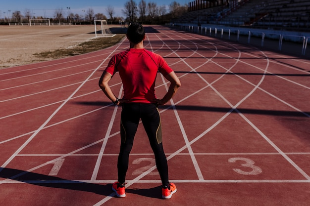 Young muscular athlete is at the start of the race tracks line at the stadium. sports concept