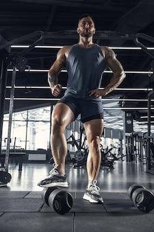 Giovane atleta muscolare che pratica in palestra, in posa fiducioso con i pesi