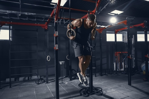 Young muscular athlete practicing pull-ups in gym with the rings
