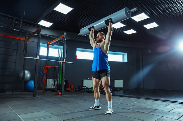 Young muscular athlete training in gym, doing strength exercises