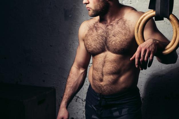 Молодой мускулистый привлекательный мужчина голый торс позирует на кольцах гимнастики
