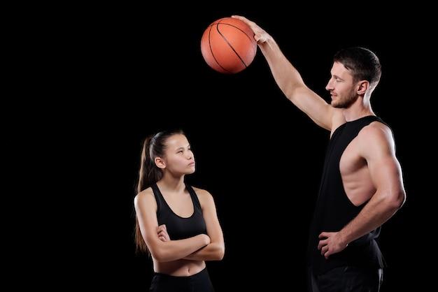 それを見て、男に耳を傾けるフィットスポーツウーマンの上にボールを保持している若い筋肉バスケットボールトレーナー