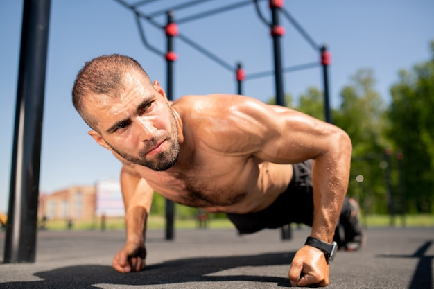 Young muscular bodybuilder standing on fists over ground while doing push-ups during workout outdoors
