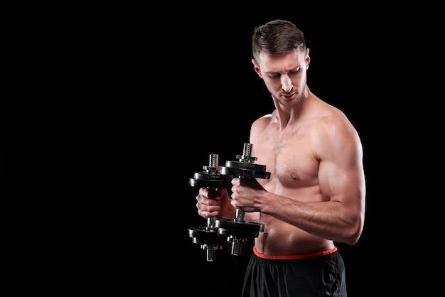 黒い壁に立っている間上腕二頭筋のための難しい運動をしているバーベルを持つ若い筋肉のボディービルダー