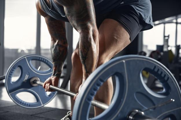 バーベルでジムで懸垂を練習している若い筋肉の白人アスリート。