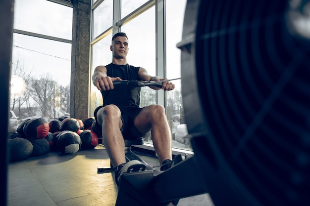 Young muscular caucasian athlete training in gym, doing strength exercises, practicing. male model work on his upper and lower body.