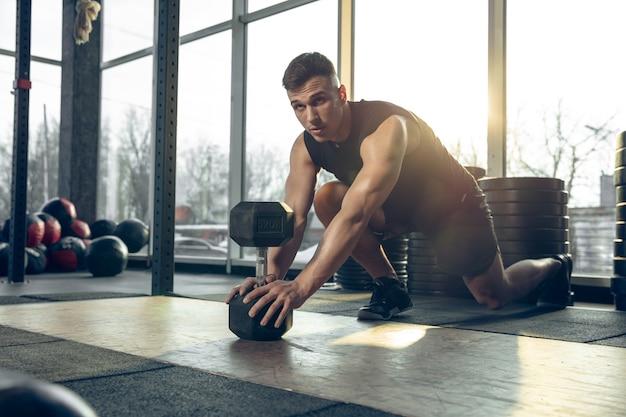 젊은 근육질의 백인 운동선수는 체육관에서 훈련하고, 근력 운동을 하고, 연습하고, 웨이트 롤링으로 상체에서 일합니다.