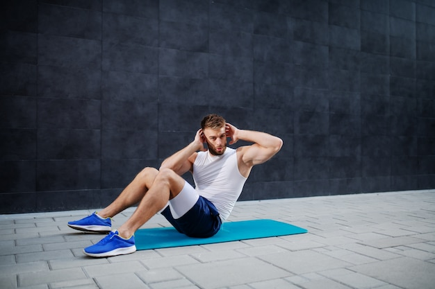 Young muscular caucasian handsome man in shorts and t-shirt doing abs on mat outdoors. in background is gray wall.