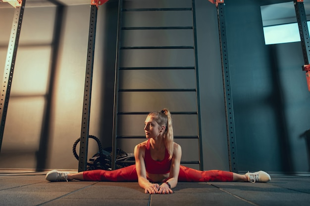 Young muscular caucasian woman practicing in gym. athletic female model doing strength exercises, training her lower, upper body, stretching.