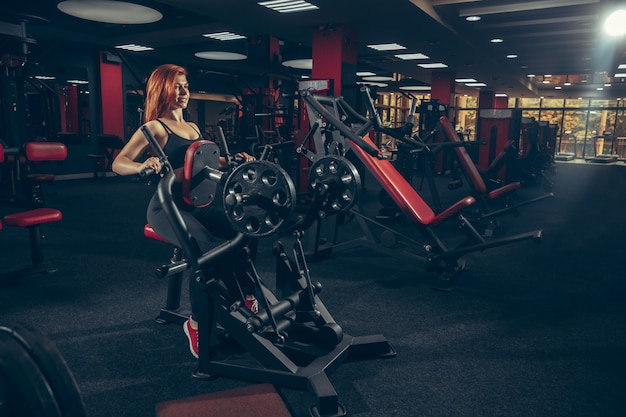 Young muscular caucasian woman practicing in gym with equipment. wellness, healthy lifestyle, bodybuilding.