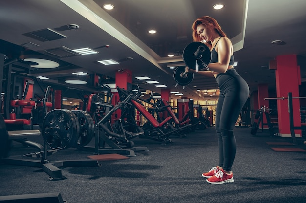 Young muscular caucasian woman practicing in gym with equipment wellness healthy lifestyle