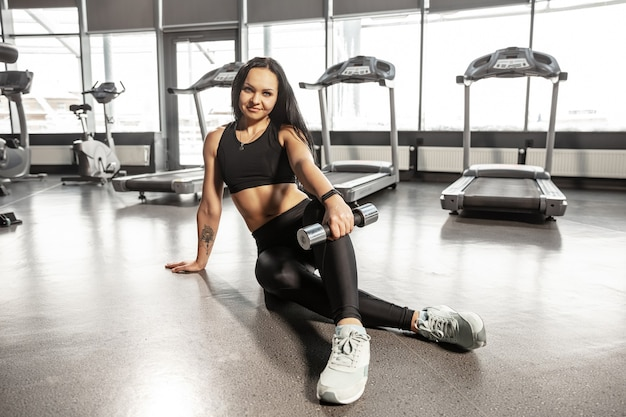 Young muscular caucasian woman practicing in gym with equipment