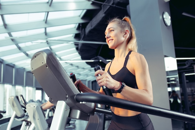 ジムで有酸素運動をしている若い筋肉の白人女性。上半身を鍛えながら筋力トレーニングをするアスリート女性モデル。ウェルネス、健康的なライフスタイル、ボディービルのコンセプト。