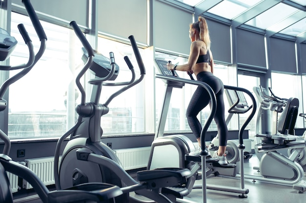 ジムで有酸素運動をしている若い筋肉質の白人女性。上半身を鍛えながら筋力トレーニングをするアスリート女性モデル。