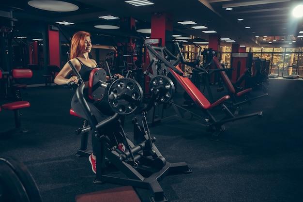 設備の整ったジムで練習して若い筋肉白人女性。ウェルネス、健康的なライフスタイル、ボディービル。